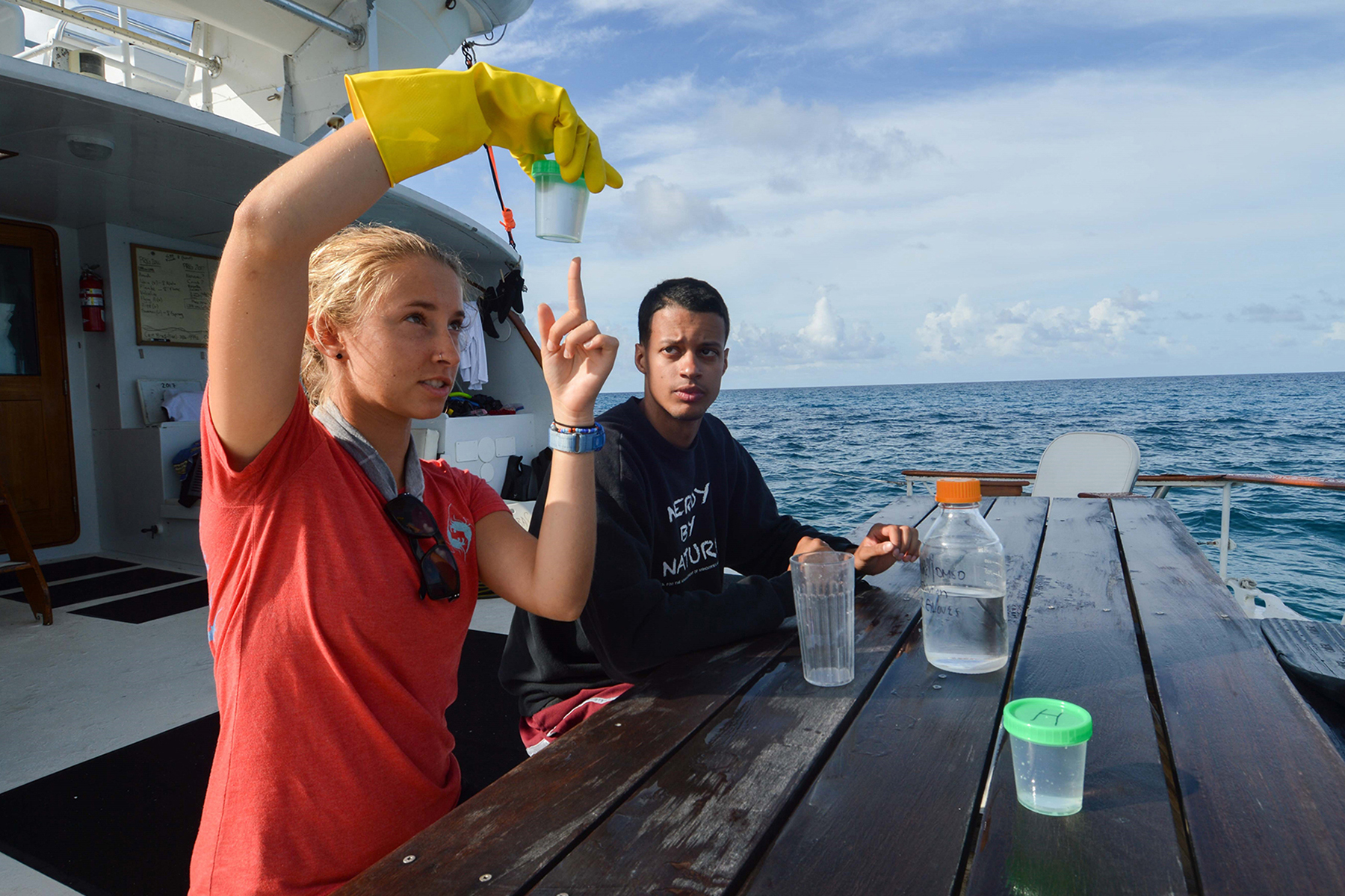 a young girl points to the specimen container she's holding while sitting on the deck of a ship