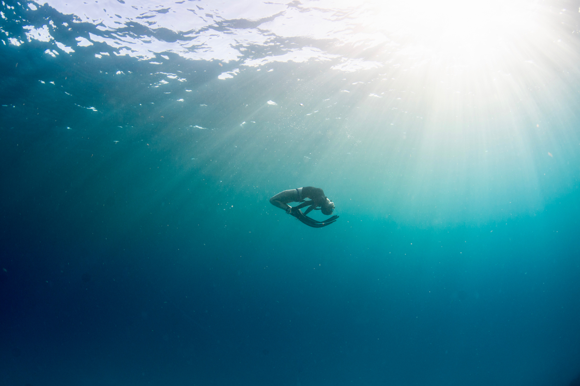 a young girl wearing a mask and flippers rests is suspended in the ocean, freediving