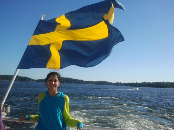 Hasan stands on a boat in front of the Swedish flag