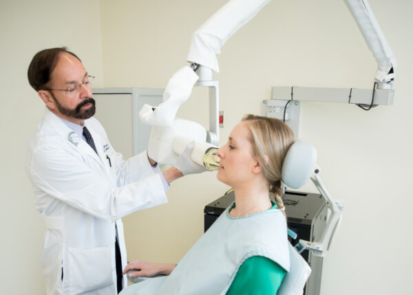 Enrique Platin takes a dental X-ray of a young woman