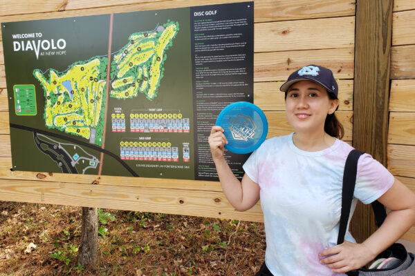 Maggie Melo holds a disc gold frisbee