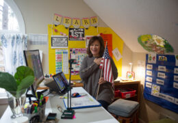 Suzanne Zaccardo holds an American flag in front of her computer to lead her online class in the Pledge of Allegiance