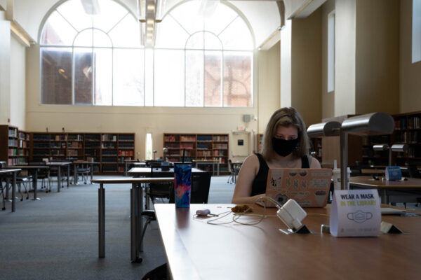 a masked UNC study sits at a desk with her laptop in Davis Library
