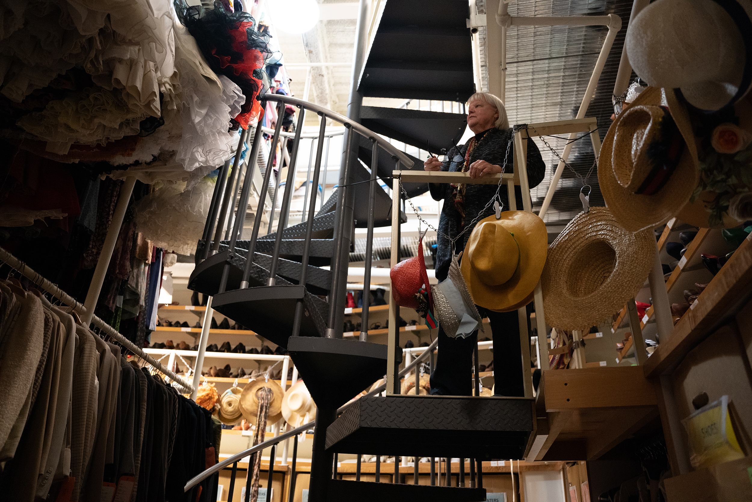 Bobbi Owen stands on scaffolding overlooking a costume storage room