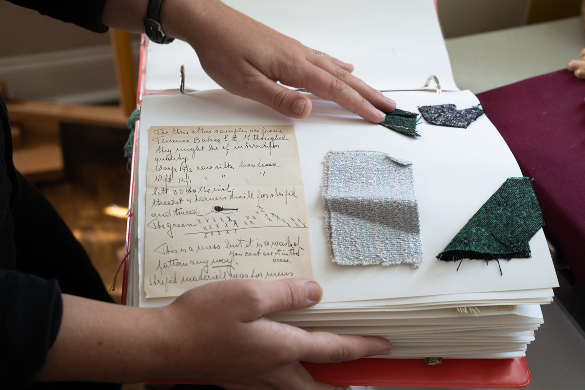 Photo: A pair of hands holding a large scrapbook. The book is open to a page containing several woven fabric samples and a handwritten note.