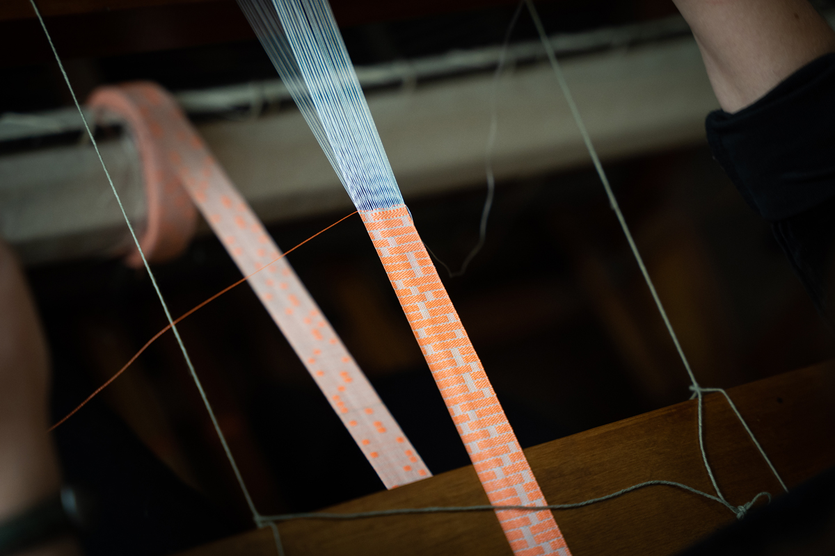 Photo: A long piece of fabric made of interwoven white and orange threads is stretched on a loom. The threads form a pattern reminiscent of a genetic sample test.