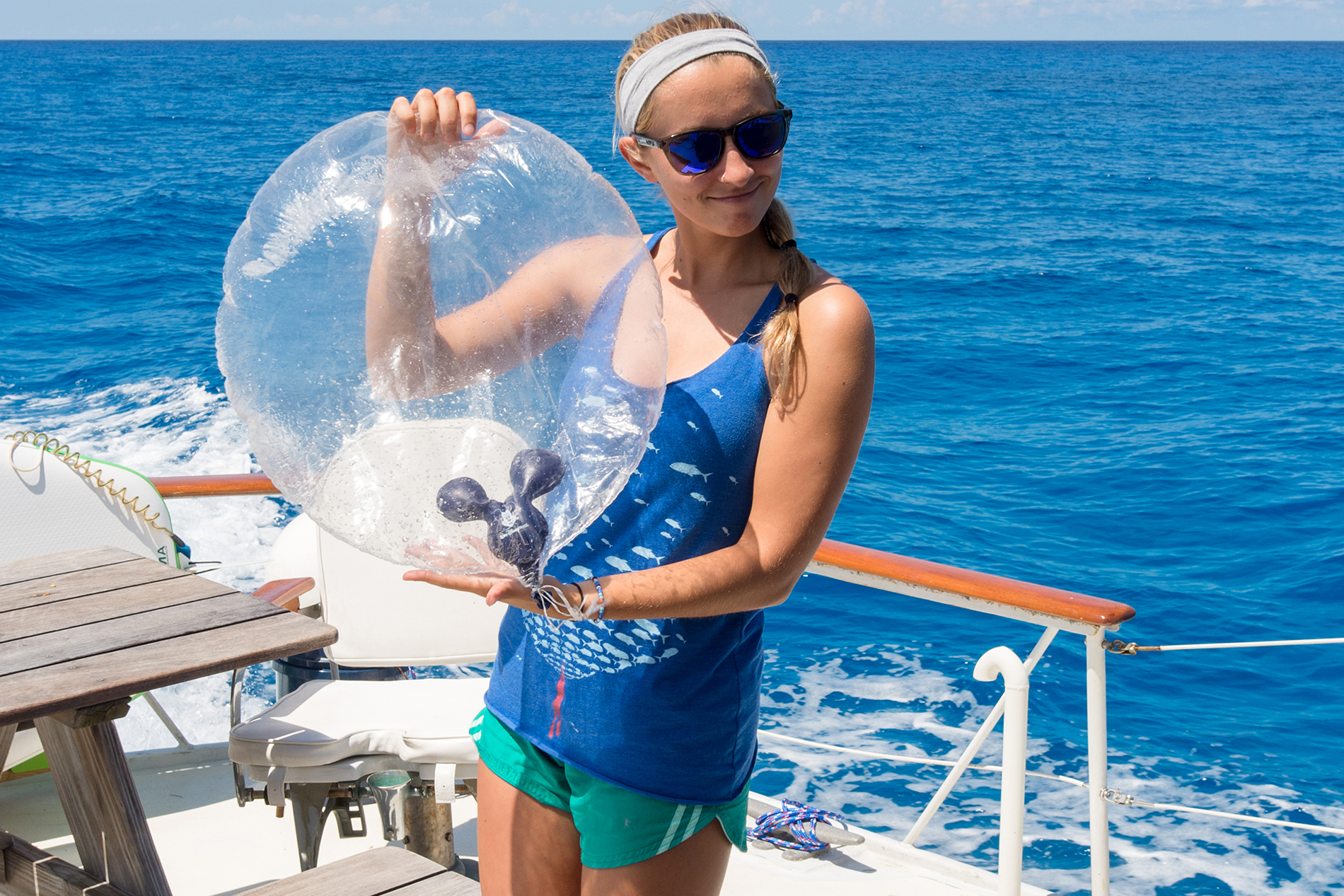 a young girl stands on a boat and holds a washed up balloon from Walt Disney World