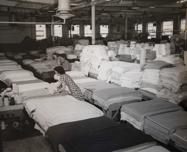 a black and white photo of a woman sorting towels in a manufacturing facility