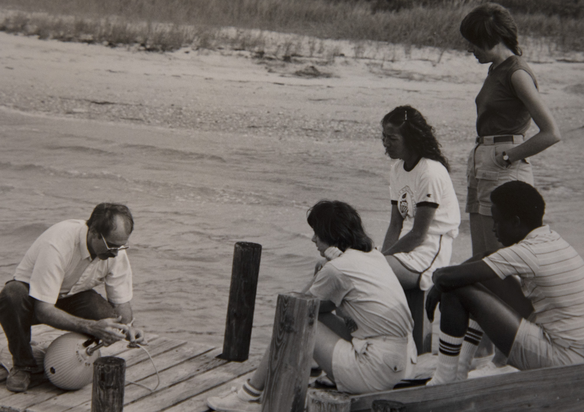 an older man shoes a group of young people how to do sediment sampling