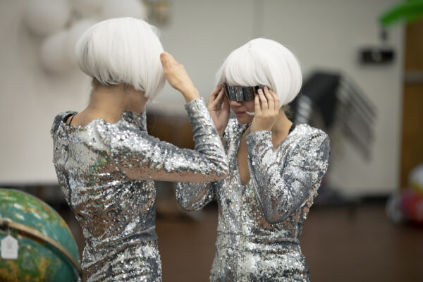 two female students hold their futuristic sunglasses against their faces and check their wigs