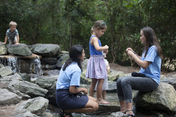 Maribel Herrera and Chloe Schneider sit on rocks in a stream and talk to a young girl