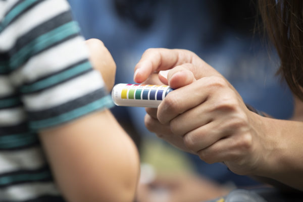 a finger pointing to the different colors on a pH test tube