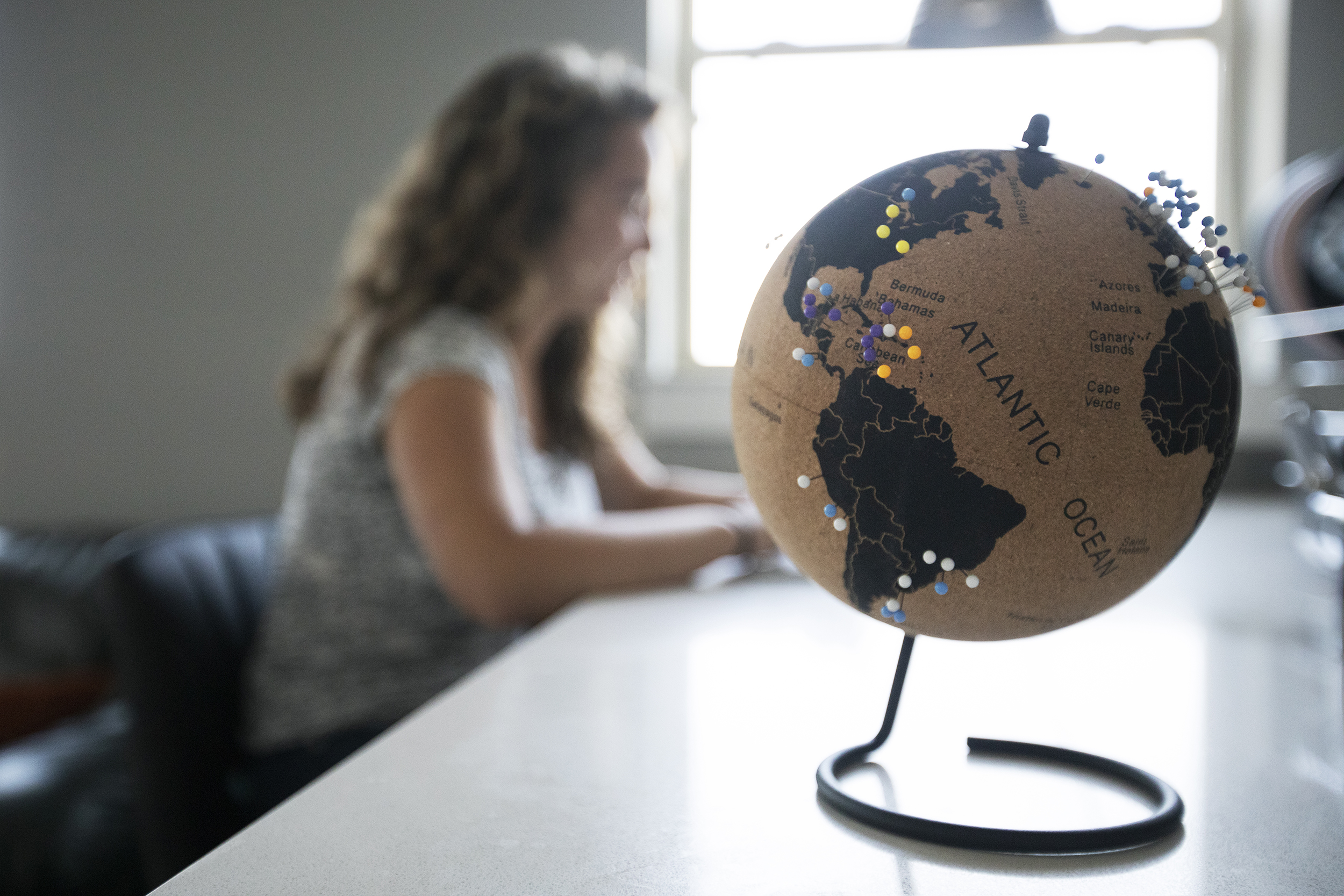 a globe full of push-pins as Kay works in the background