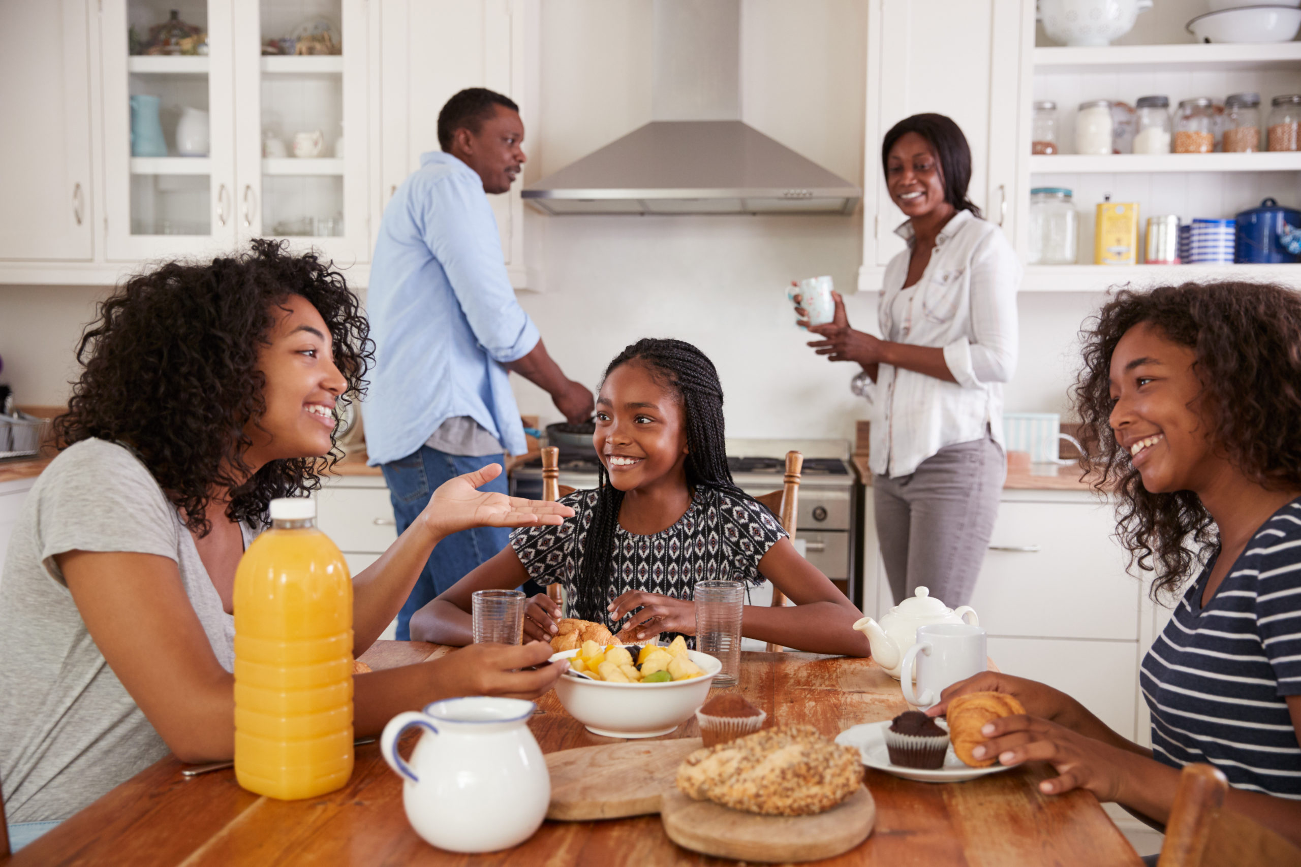 Family With Teenage Children Eating Breakfast In Kitchen