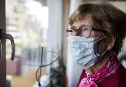 an elderly woman wearing a mask looks out the window