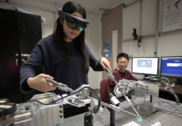 a girl wears an augmented reality headset while controlling long rods on a simulator that mimics laparoscopic surgery
