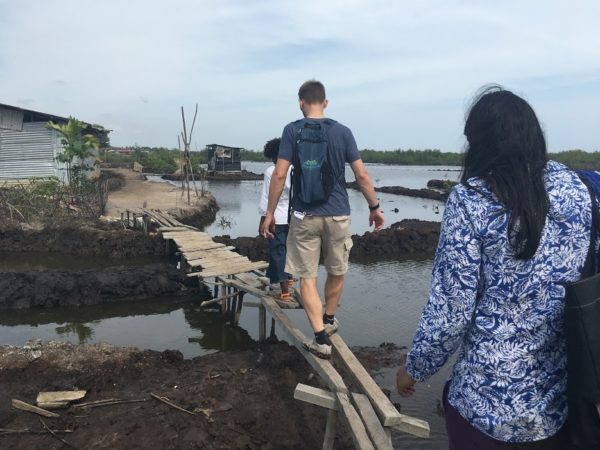 Jeff Austin and other members of the team from UNC and the CDC walk across a makeshift bridge in a neighborhood outside Monrovia.