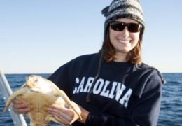 Paxton poses with a loggerhead turtle, which she released back into the water after the photo was taken.