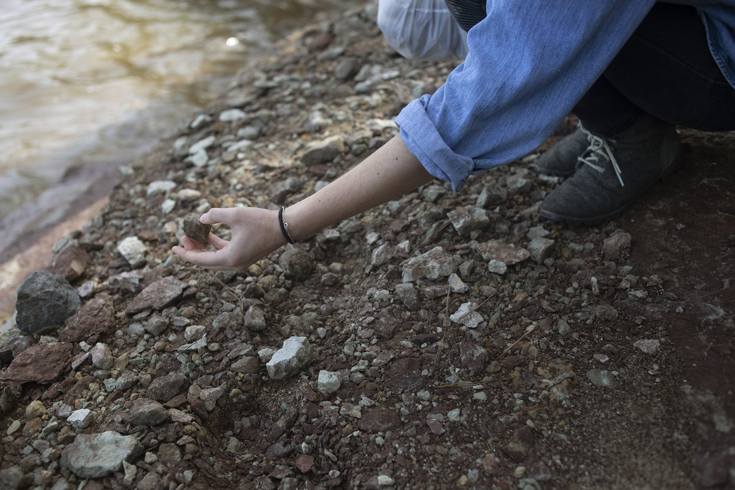 Detail shot of Ayla Gizlice's hand as she crouches and picks up a chunk of clay.