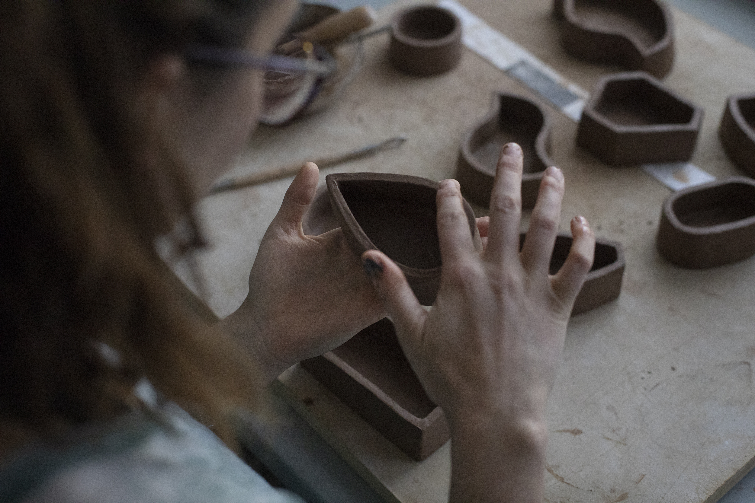 Overhead shot looking over Ayla Gizlice's shoulder as she shapes a clay vessel in her hands.
