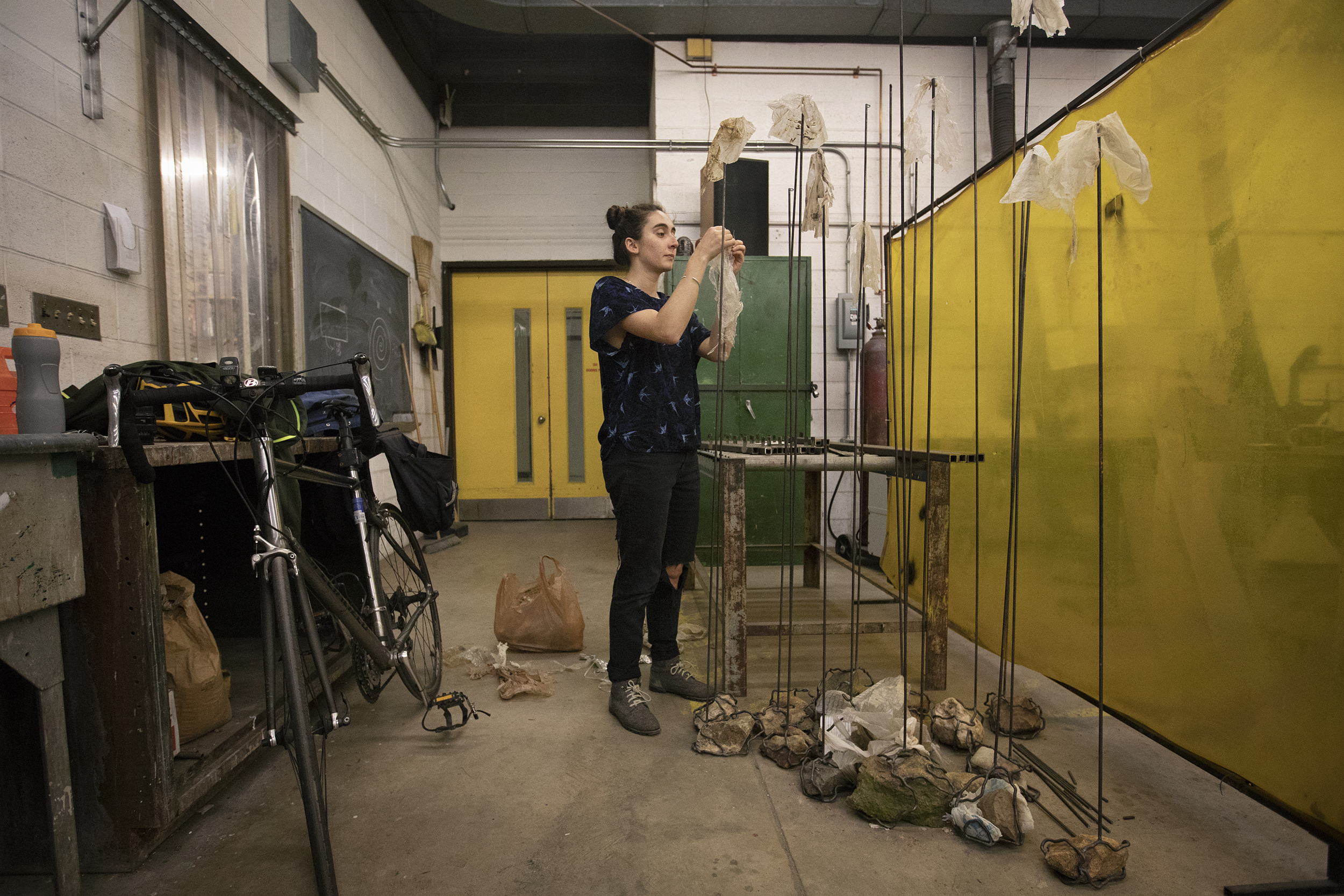 Ayla Gizlice stands in the middle of a welding shop and attaches plastic bags to large, metal stands.