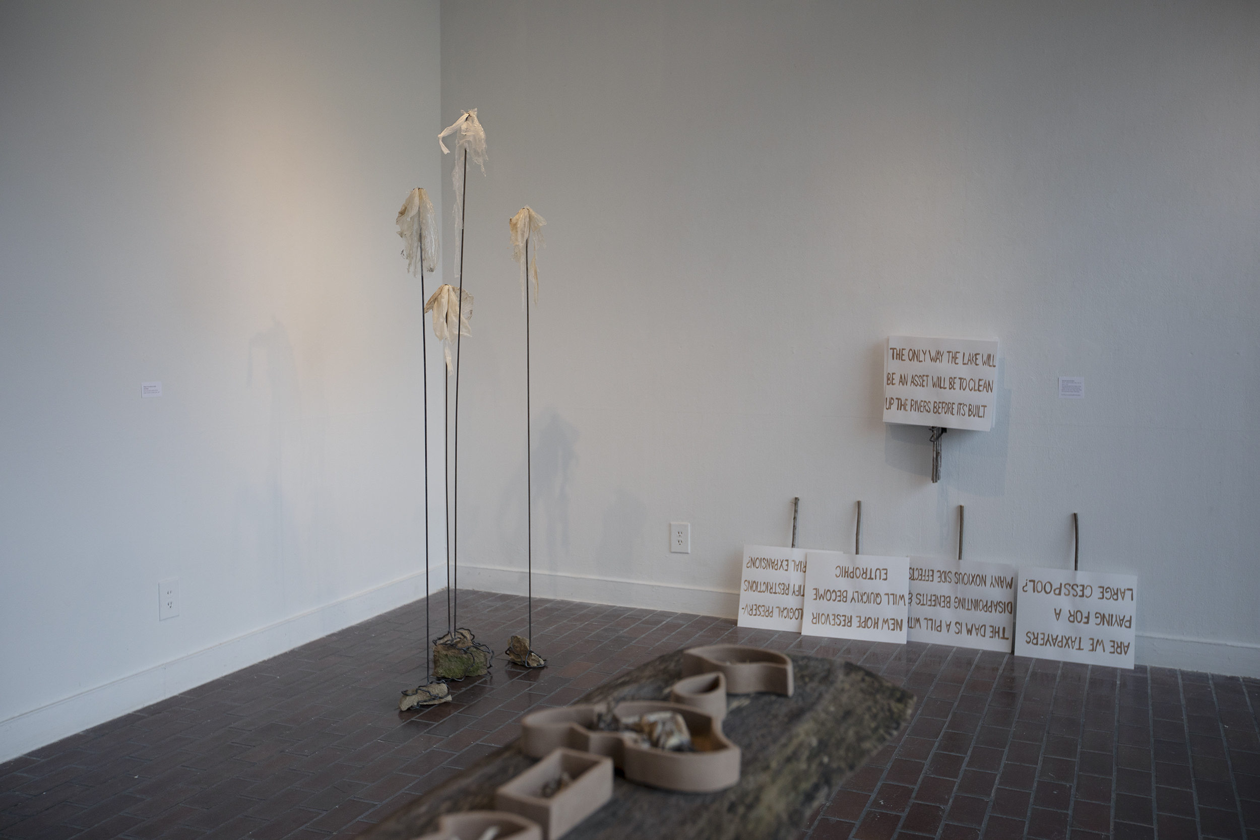 Detail shot of Ayla Gizlice's project, showing the metal stands withe plastic bags attached, picket signs lined against the wall, and clay vessels holding fish bones on a table.