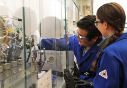 a woman and a man in blue lab coats lower the pressure gage on technical equipment inside a lab