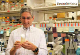 a 40-something male holds a container of fruit flies -- shelves with colorful labels are in the background