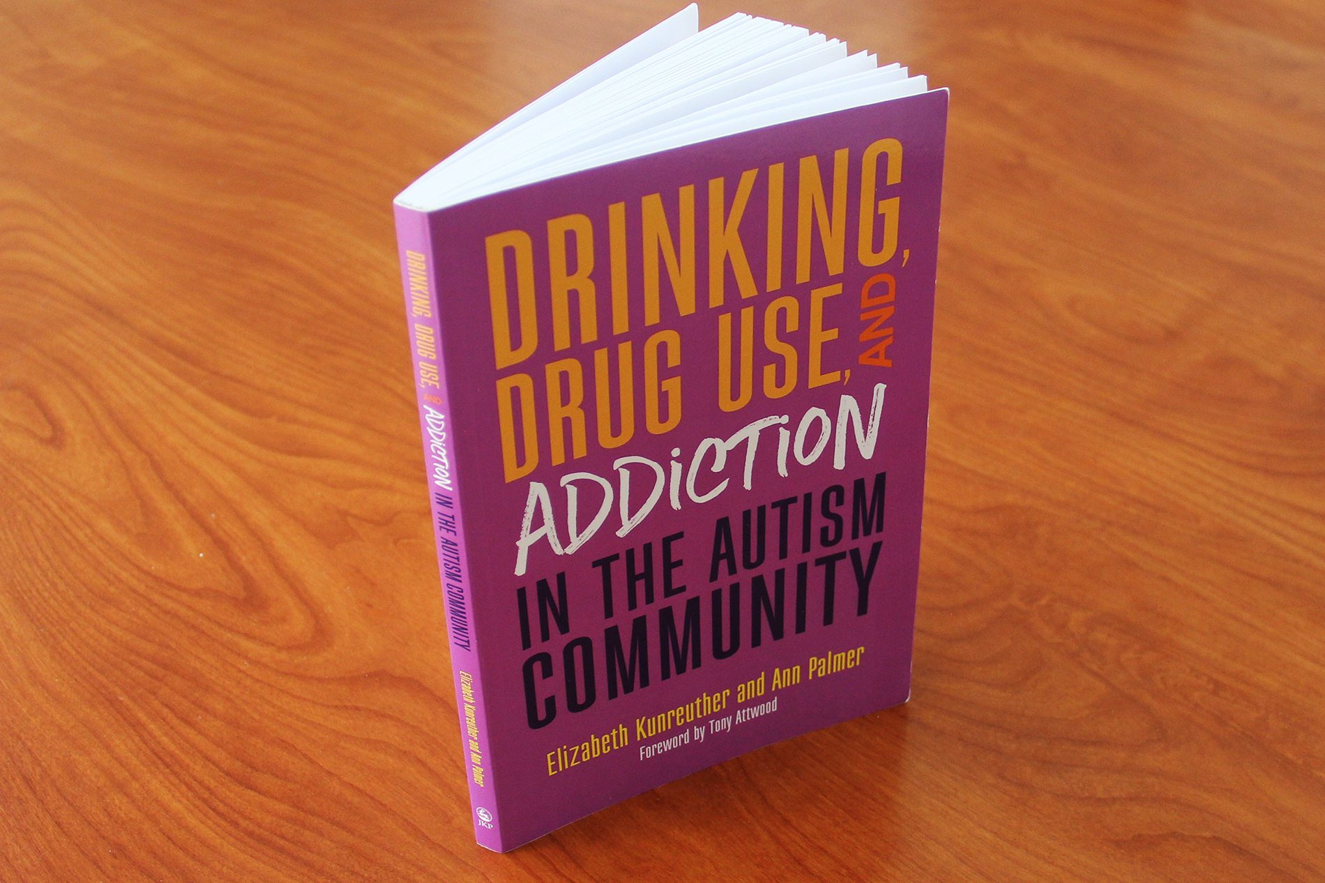 "the book ""Drinking, Drug Use, and Addiction in the Autism Community"" sits on a wooden table"