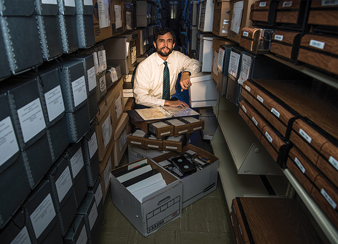 Bryan Giemza surrounded by boxes of manuscripts, VHS tapes, and files