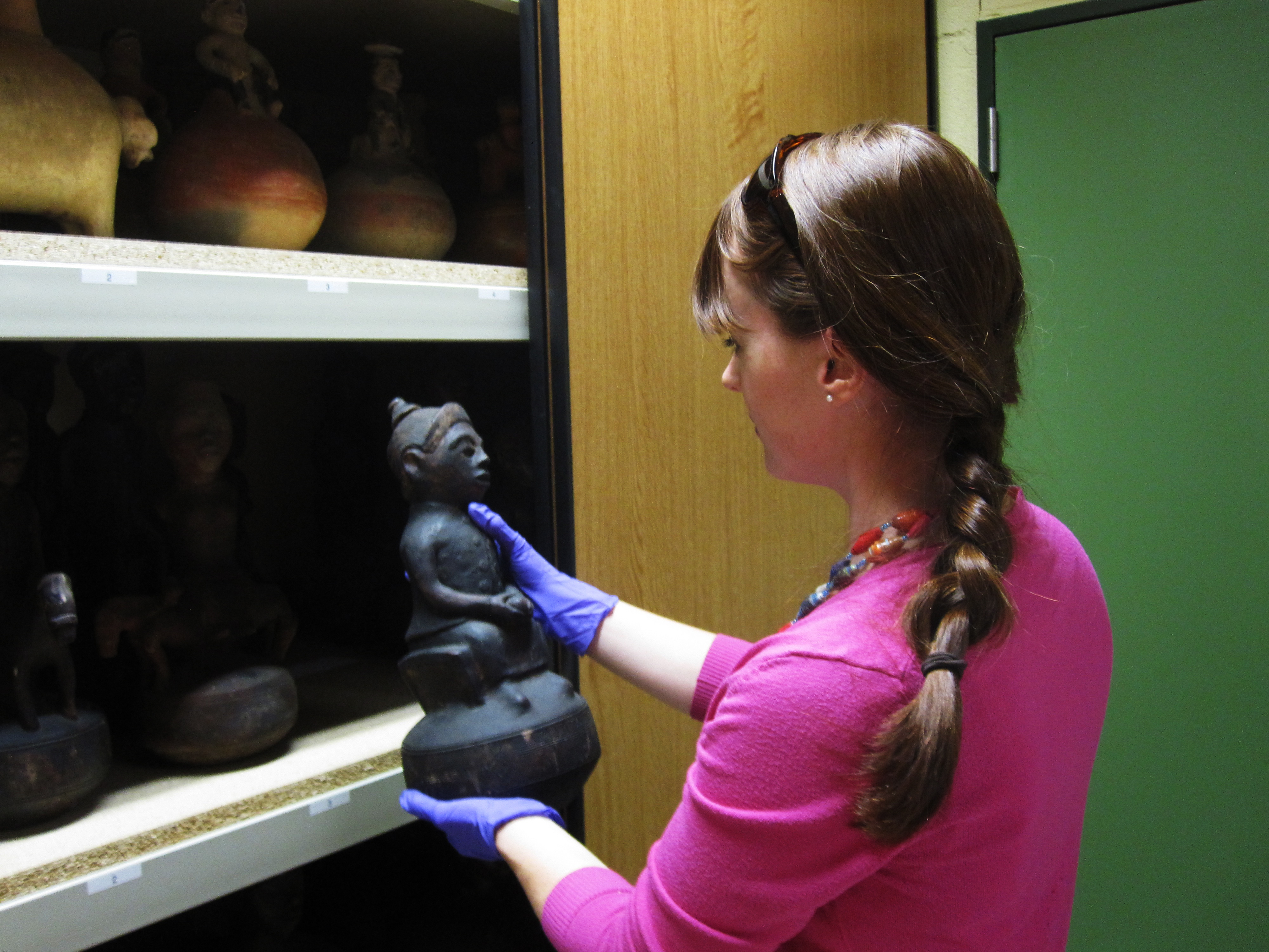 Researcher Carlee Forbes pulls a statue from a cabinet.