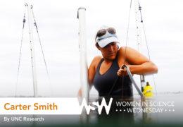 Carter Smith works on marine science equipment in waist deep water.