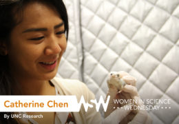 a young female researcher holds a frog