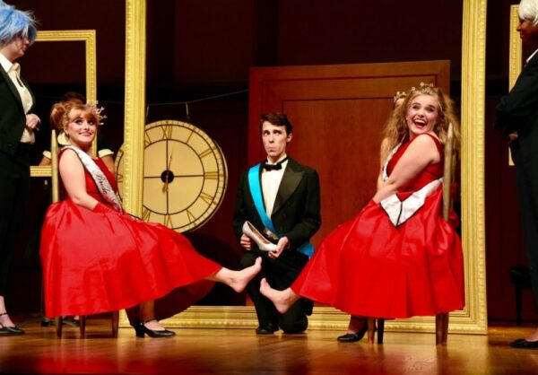 a young man in a tuxedo holds a show as two young women in bright red dresses sit with their feet pointed out on either side of him