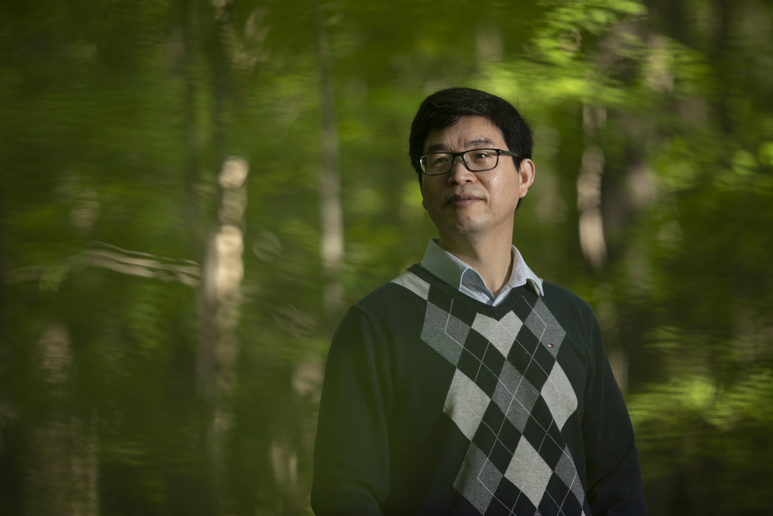 Conghe Song stands for a portrait in a forest.