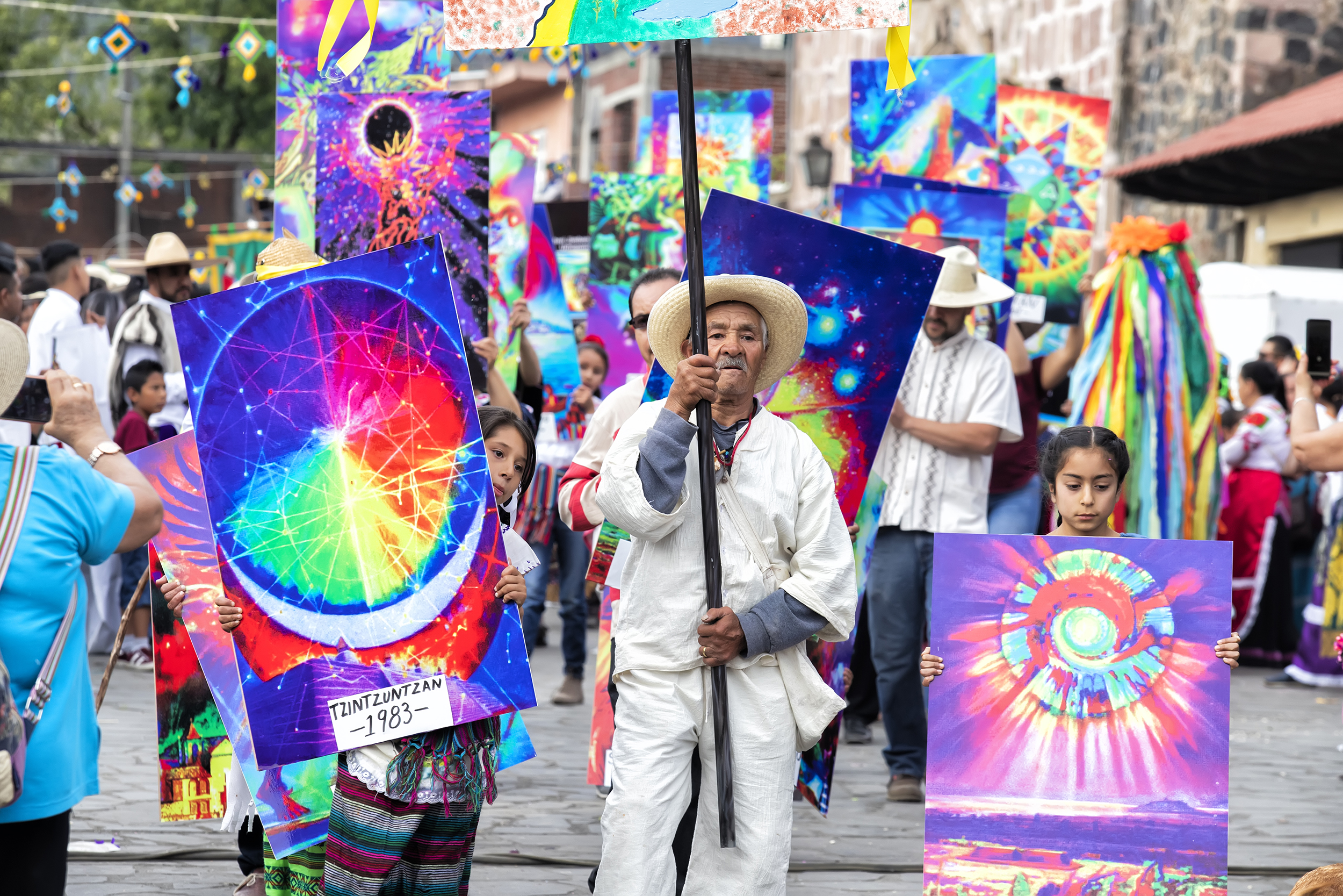 an elderly man and two young girls hold colorful signs while walking down a street in Mexico