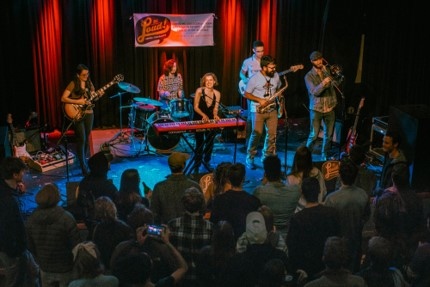 Rachel Despard plays the keyboard on a stage and is surrounded by her band and a live audience