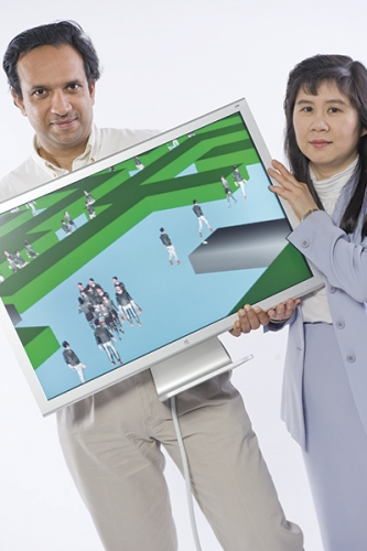 Steve Exom Dinesh Manocha and Ming Lin hold a computer showcasing a modeling and simulation program.