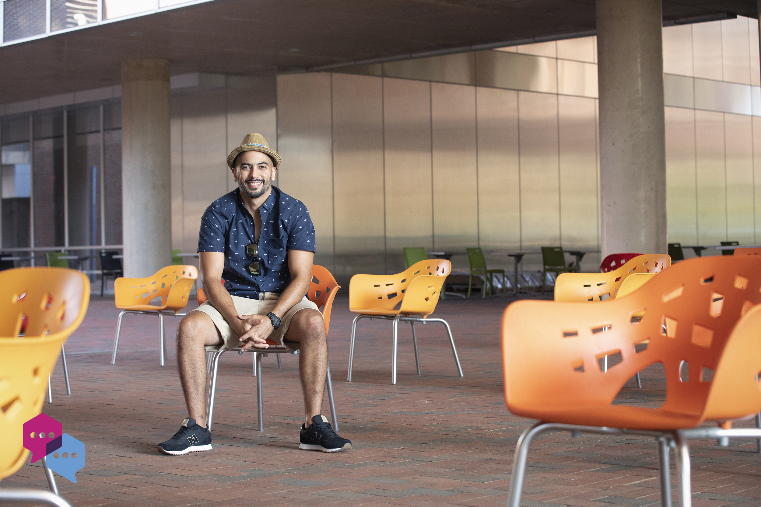 Esteban Agudo sits in a orange chair in the quad of the Genome Sciences Building