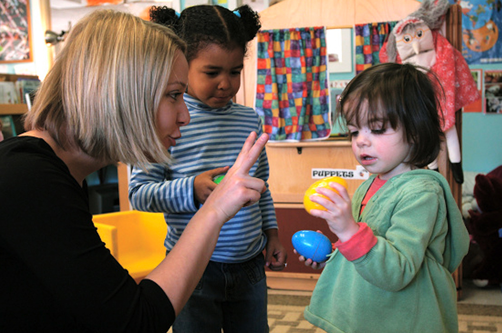 a blond woman holds two fingers up to a toddler, trying to teach her how to count