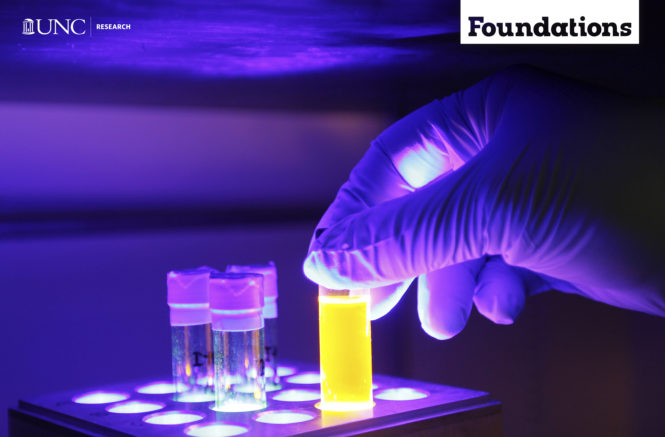 a blacklight makes everything purple while a gloved hand places a test tube full of yellow fluid into a a test tube tray