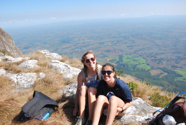 two young girls sit on the top of a mountain in Malawi