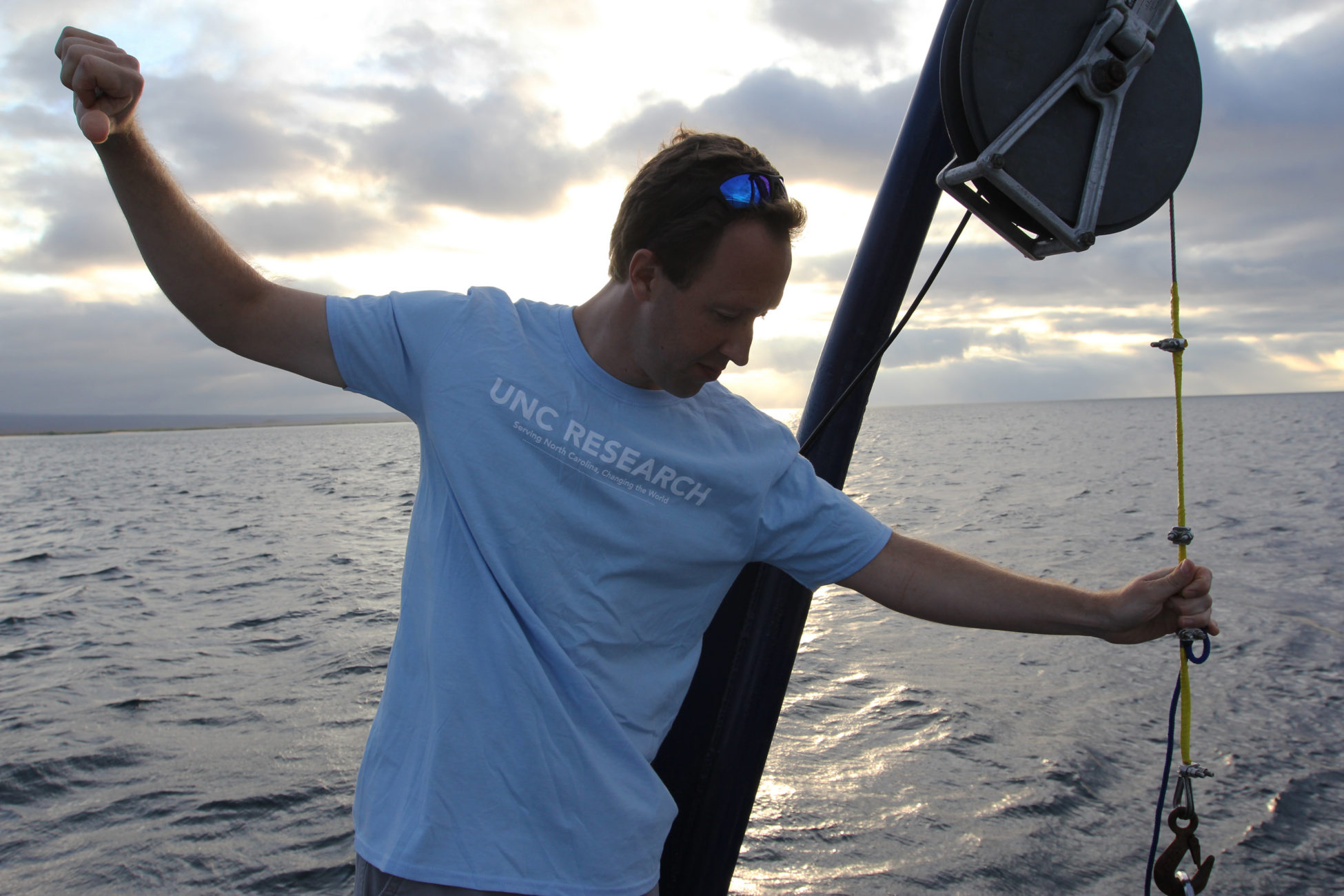 Picture of Scott Gifford on-board the Sierra Negra, giving hand signals while prepping their research equipment.