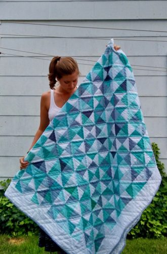 Alyssa Grube holds up a blue and white quilt