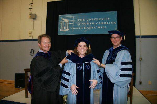 Kevin Guskiewicz, Johna Register-Mihalik, and Jason Mihalik at Johna's doctoral hooding ceremony