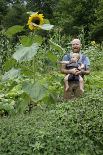 Chad Stevnes Heartwood stands in his garden with son Osha