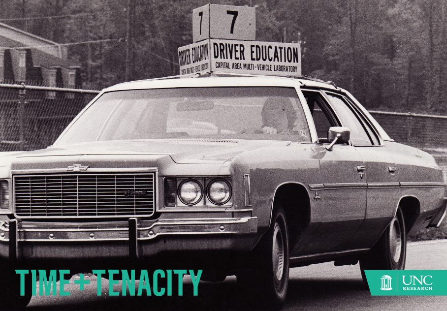 "Old image of a researcher sitting in a car, with a sign on the top of it saying ""7; Driver Education. Captial Area Multi-Vehicle Laboratory"""