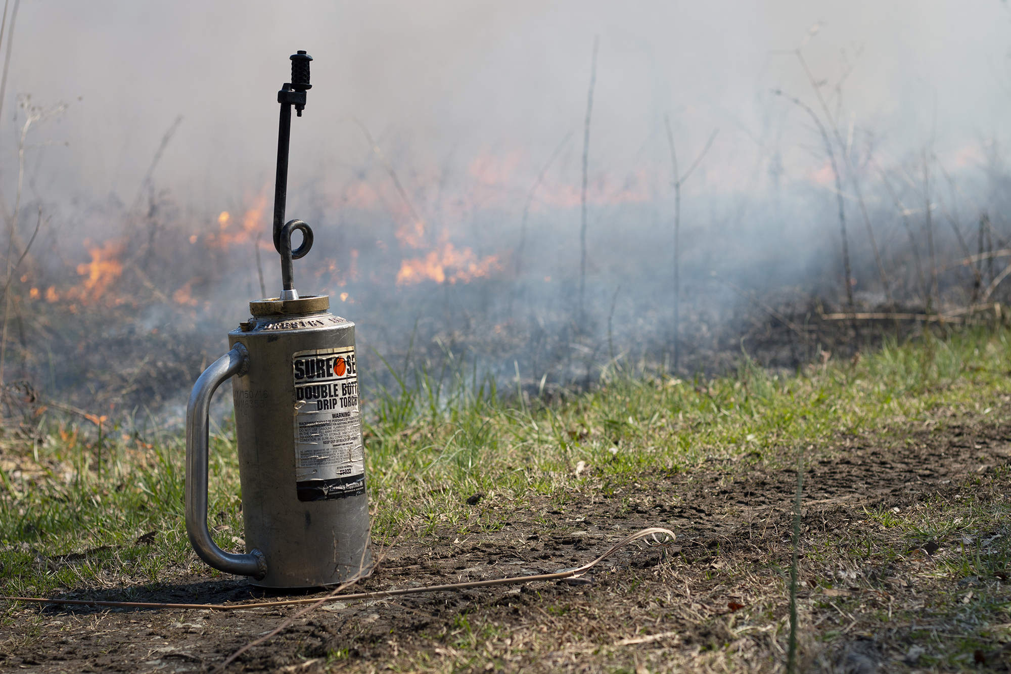 a driptorch sits on the side of the road as a fire burns in the background