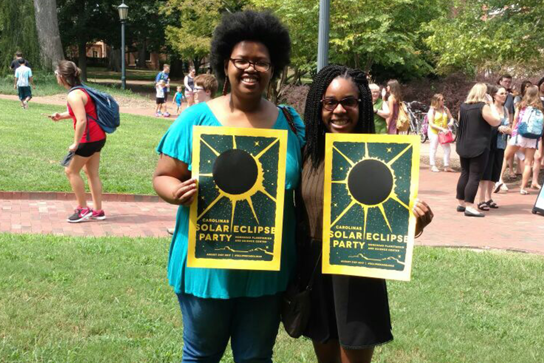 two young African-American girls hold solar eclipse posters