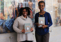 "Tanya Shields and Kathy Perkins hold up the book ""Help Me to Find My People"" by former UNC-Chapel Hill professor, Heather Williams."